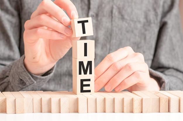 La mano mette un cubo di legno con la lettera t dalla parola time