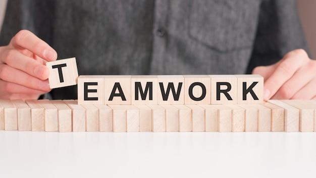 La mano mette un cubo di legno con la lettera lavoro di squadra