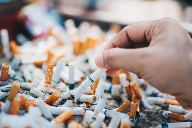 Mano che mette la sigaretta su un posacenere con mozziconi di sigaretta conficcati nella cenere