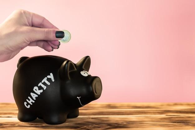 Mano che mette una moneta in un salvadanaio nero con un'etichetta di beneficenza in gesso su uno sfondo rosa, donazione e concetto di beneficenza. copia spazio.