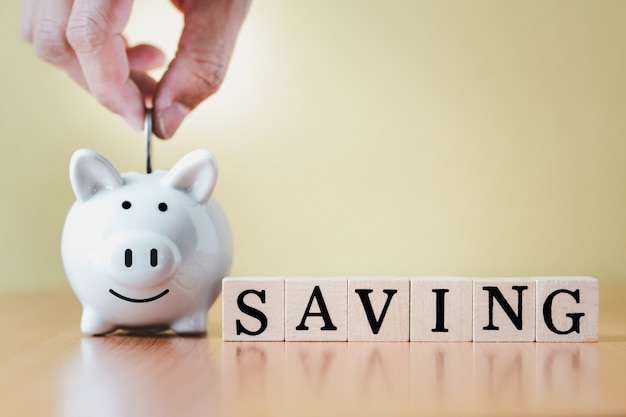 Mano che mette la moneta nel salvadanaio bianco e nella scatola di legno con il salvataggio della parola tag per la pianificazione del passaggio alla crescita, il risparmio di denaro per il fondo pensione e il concetto di piano futuro.