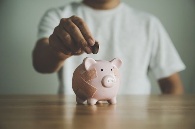 Mano che mette moneta nel salvadanaio sul tavolo di legno. concetto di risparmiare denaro e finanziare investimenti aziendali