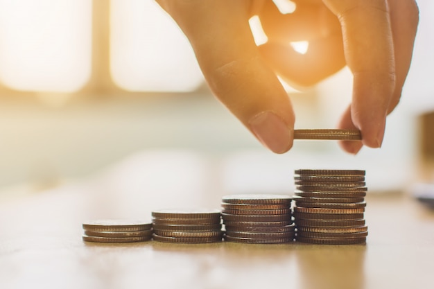 Passi mettere la scala di punto della pila della moneta sullo scrittorio