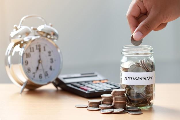 Mano che mette le monete in un barattolo di vetro con calcolatrice e sveglia per risparmiare tempo per il concetto di pensione, pianificazione della pensione.