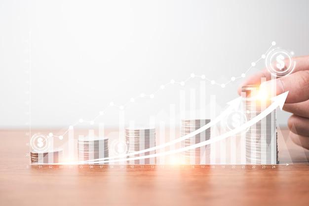 Passi mettere le monete che impilano con il grafico virtuale e aumenti la freccia davanti all'uomo d'affari. investimento aziendale e concetto di profitto di risparmio.