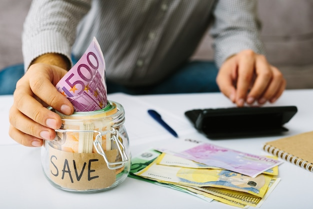 Mano mettendo banconote in euro in barattolo di vetro per il risparmio. uomo che fa la sua contabilità