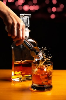 Mano mettendo il ghiaccio in un bicchiere di whisky accanto a una bottiglia e sfondo nero