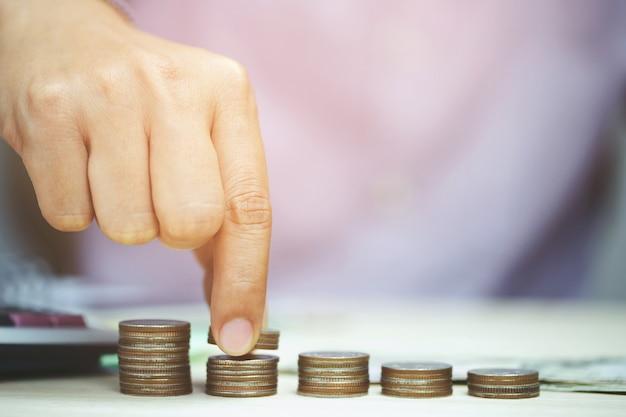 Pila di monete mettendo mano soldi in crescita, risparmiando denaro per concepte scopo