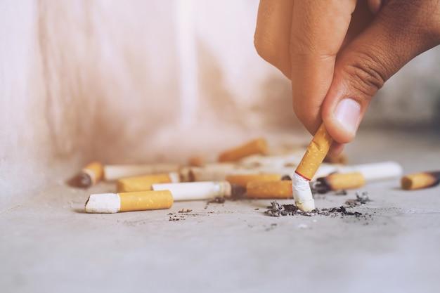 Mano che mette fuori una sigaretta, mozzicone di sigaretta sul pavimento di cemento, cemento nudo.