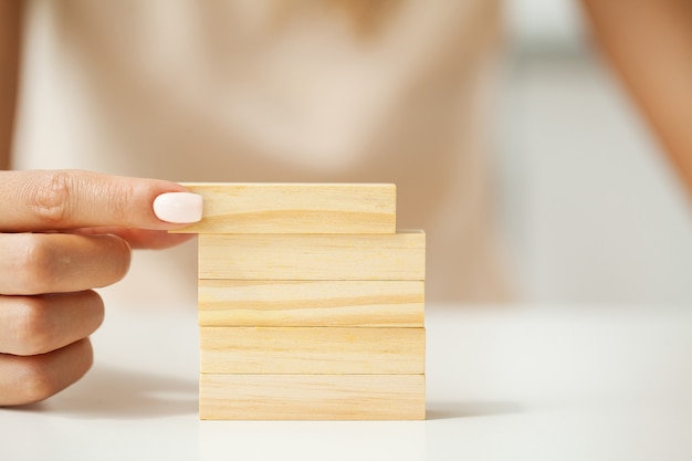 Mettendo a mano e impilando cubi di legno vuoti sul tavolo con lo spazio della copia per la formulazione di input e l'icona infografica.
