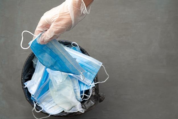 Mettendo mano maschera chirurgica sporca usata in un bidone della spazzatura. avvicinamento.