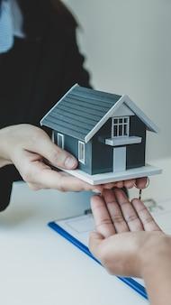 Affida a un agente immobiliare il modello di casa e spiega il contratto di lavoro, l'affitto, l'acquisto, il mutuo, il prestito o l'assicurazione sulla casa alla donna acquirente.