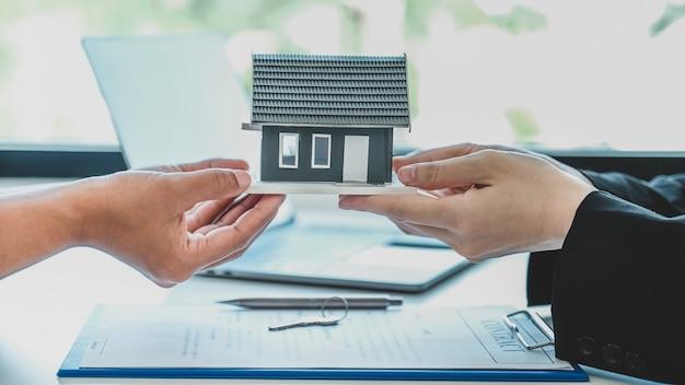 Consegna a un agente immobiliare il modello della casa e spiega il contratto commerciale, l'affitto, l'acquisto, l'ipoteca, il prestito o l'assicurazione sulla casa alla donna acquirente.