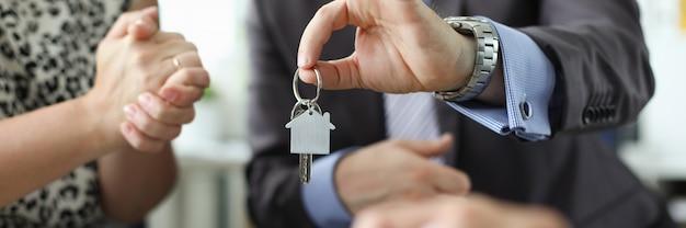Mano dell'agente dell'aganista chiave della casa della stretta dell'agente immobiliare