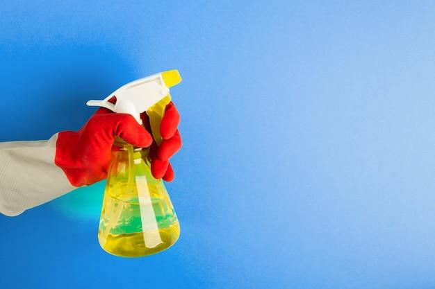 Una mano in un guanto rosso tiene uno spruzzo di liquido detergente su una superficie blu