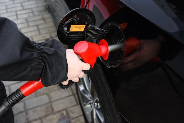 Mano che riempie la macchina con il carburante alla stazione di servizio.