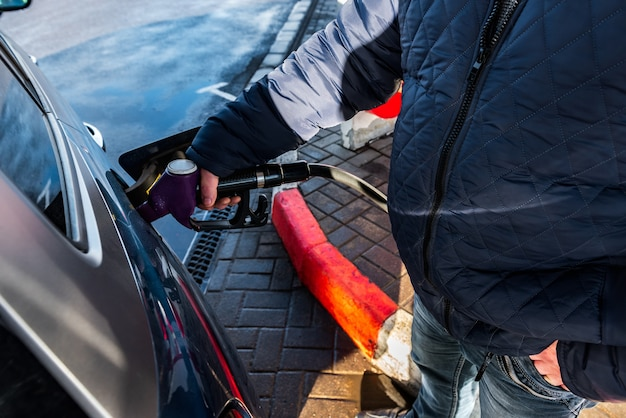 Rifornimento manuale dell'auto con carburante presso la stazione di rifornimento