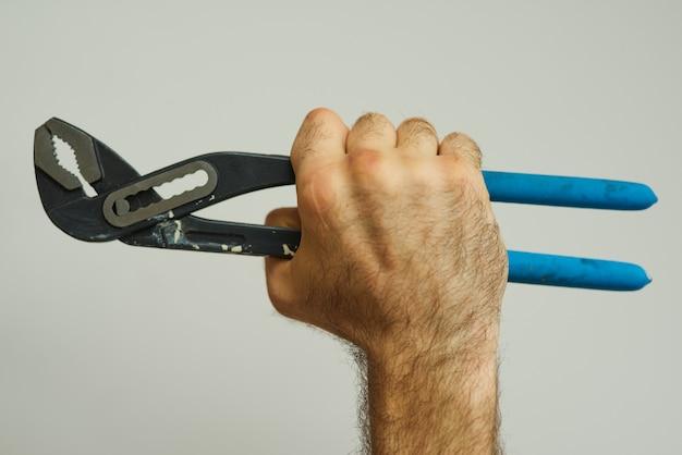 Mano del riparatore che tiene una chiave a tubo con manico blu su sfondo bianco