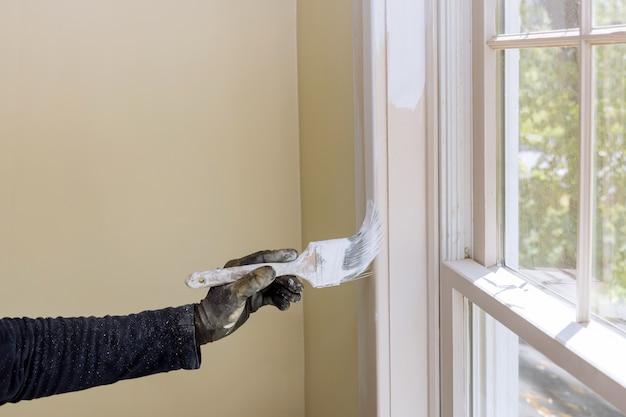 Mano del riparatore che dipinge con i guanti nel rivestimento della modanatura della finestra della pittura