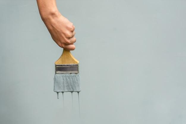 La mano di un riparatore con un pennello dipinge il muro di blu.
