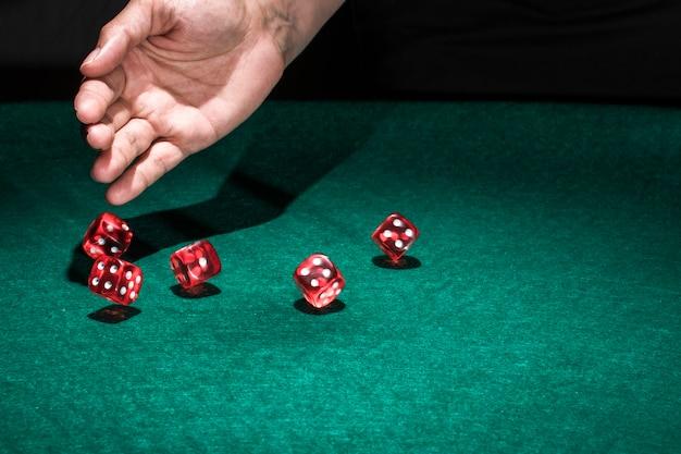 Mano che rotola i dadi sul tavolo da poker