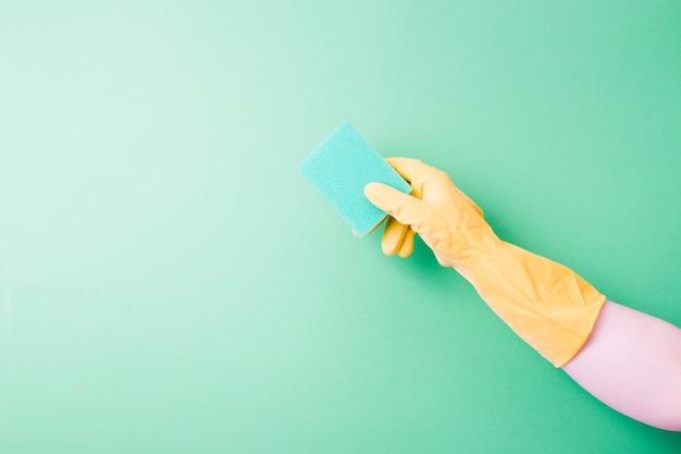 Una mano in un guanto di gomma tiene uno sfondo verde spugna verde