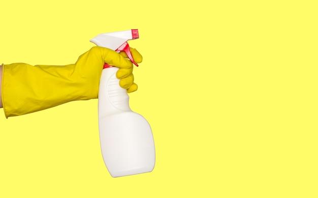 Una mano in un guanto di gomma tiene una pistola a spruzzo con un agente detergente o disinfettante