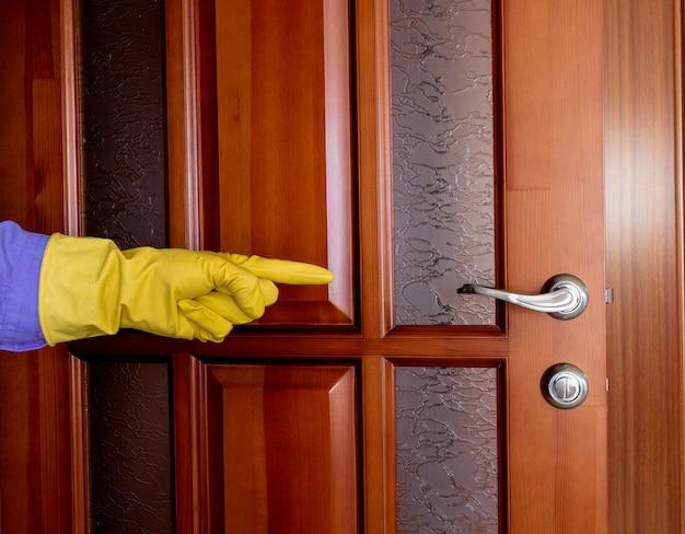 La mano in un guanto di gomma indica la maniglia della porta. disinfezione durante l'epidemia di virus. pulizia dell'appartamento. pulizia della maniglia della porta