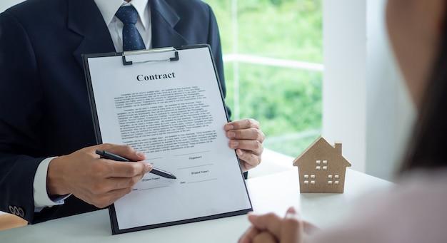 La mano del reparto vendite o dell'uomo d'affari indica la posizione per firmare il contratto. il responsabile delle vendite spiega i termini di un contratto di acquisto o locazione, ipoteca di terreni o immobili.