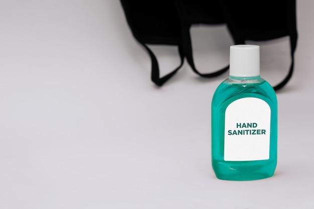 Bottiglia del prodotto disinfettante della mano e maschere di protezione mediche nere isolate su fondo bianco con lo spazio della copia