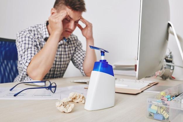 Disinfettante per le mani sulla scrivania del designer dell'interfaccia utente che ha mal di testa dopo aver lavorato tutto il giorno con clienti difficili