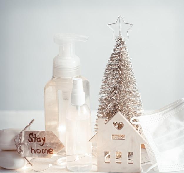 Igienizzante per le mani, maschere per il viso usa e getta, dettagli di decorazioni natalizie su pareti chiare sfocate. concetto di pandemia di natale e coronavirus. covid-19.