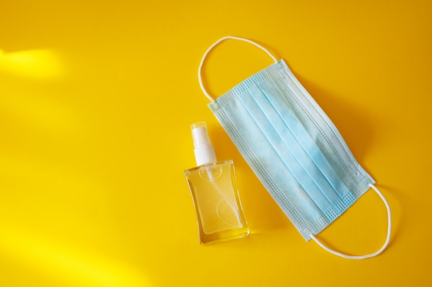 Igienizzante per le mani e maschera protettiva medica sul tavolo giallo