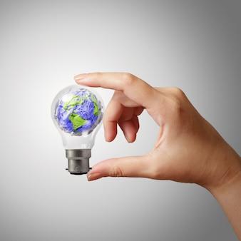 Mano che mostra il simbolo di carta sgualcito del mondo in lampadina