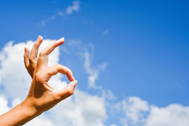 La mano mostra il gesto giusto. mano della donna che dà è segno giusto. copia spazio.