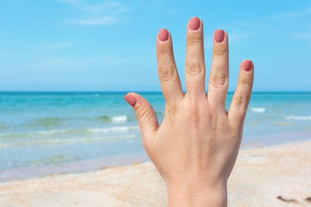La mano firma sopra il mare e il cielo blu, il viaggio dell'estate, concetto di vacanza di festa