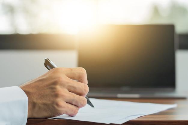 Firma a mano sul documento, mano che tiene la scrittura a penna