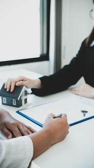 Firma del contratto a mano dopo che l'agente immobiliare ha spiegato all'acquirente il contratto di lavoro, l'affitto, l'acquisto, il mutuo, il prestito o l'assicurazione sulla casa.