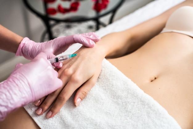 Biorivitalizzazione della pelle delle mani. nell'ufficio del cosmetologo, un'iniezione al polso. guanti rosa, un asciugamano bianco.
