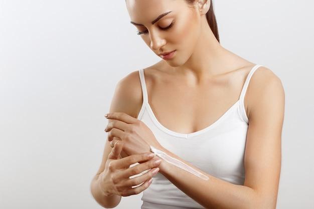 Cura della pelle delle mani close up delle mani femminili che applicano lozione crema