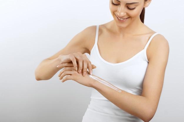 Cura della pelle delle mani le donne usano lozione per il corpo sulle braccia. donna che applica la crema alle mani