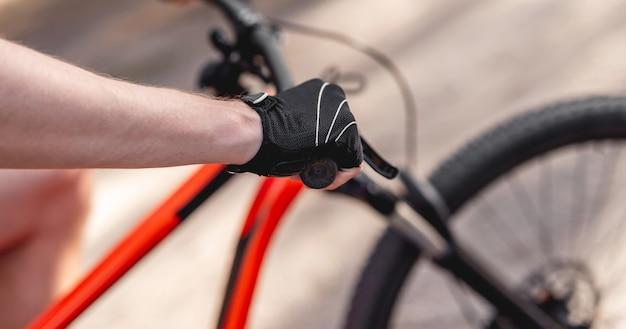Mano in guanto sportivo sul manubrio della bicicletta