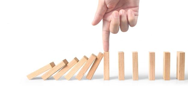 Mano che arresta effetto di domino su bianco