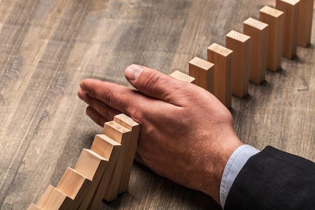 Mano che ferma i domino che cadono, concetto di affari