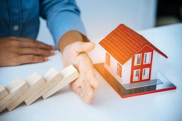 La mano ferma il rischio che i blocchi di legno cadano sulla casa, l'assicurazione sulla casa, la sicurezza e il concetto di gestione del rischio.