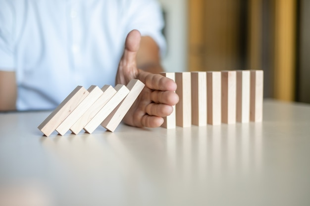 Mano che impedisce ai blocchi di legno di cadere nella linea del domino