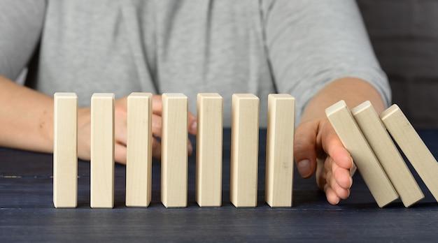 La mano arresta la caduta delle barre di legno su una superficie blu. il concetto di una personalità forte e coraggiosa capace di resistere a difficoltà impari. affari forti, controllo della situazione