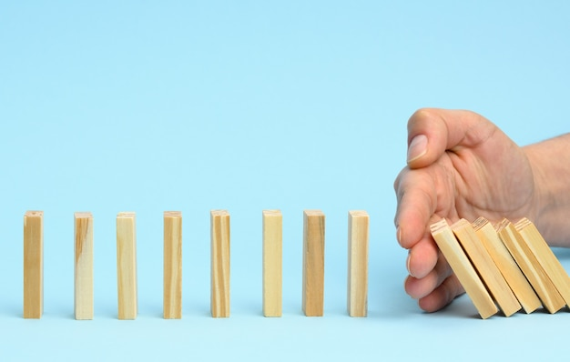 La mano arresta la caduta delle barre di legno su una superficie blu