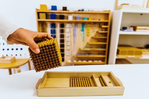 Mano di uno studente che maneggia materiale montessori all'interno di un'aula.