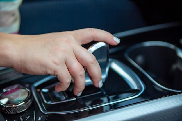 La mano cambia le modalità sul primo piano della leva del cambio automatico senza volto
